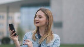 Zbliżenie portreta blondynki ładna dziewczyna wykonuje selfie na miastowym miasto ulicy tle Czerwone wargi zbiory wideo