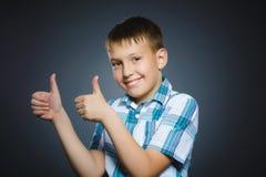 Zbliżenie portreta chłopiec przedstawienia kciuka pomyślny szczęśliwy popielaty tło up obrazy stock