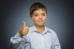 Zbliżenie portreta chłopiec przedstawienia pomyślny szczęśliwy kciuk up odizolowywał popielatego tło Obraz Stock