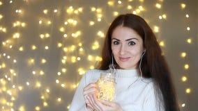 Zbliżenie portreta kobieta w hełmofonów smilling, słucha muzyka Tło z bokeh światłami zbiory wideo