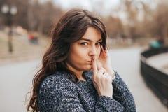 Zbliżenie portreta skryta młoda kobieta umieszcza palec na wargach zdjęcie royalty free