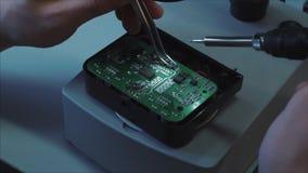 Zbliżenie pracownika ręk pracy z lutowniczym żelazem i pincetami zdjęcie wideo