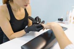 Zbliżenie proces fachowy manicure Manicurzysta kobiety ręki w czarnych rękawiczkach robi manicure'owi używać profesjonalistów nar obraz stock