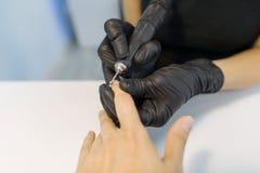 Zbliżenie proces fachowy manicure Manicurzysta kobiety ręki w czarnych rękawiczkach robi manicure'owi używać profesjonalistów nar zdjęcie royalty free