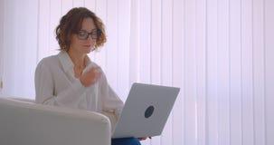 Zbliżenie profilowy portret dorosłej rudzielec caucasian bizneswoman patrzeje kamery obsiadanie w szkłach używać laptop zbiory wideo