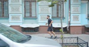 Zbliżenie profilowy portret dorosły caucasian zdecydowany męski biegacz jogging w dół ulicę w miastowym mieście outdoors zbiory wideo