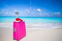 Zbliżenie różowa walizka dalej i Święty Mikołaj kapelusz Zdjęcie Royalty Free
