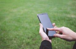 Zbliżenie ręka żeński mienia smartphone jest usytuowanym na trawie i lo Obraz Stock