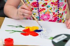 Zbliżenie ręka mała dziewczyna, trzymający muśnięcie, rysuje kolorowych kwiaty Fotografia Stock