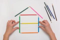 Zbliżenie ręki budują dom na kawałku papieru od kredek, wyprostowywa ściany Zdjęcie Stock