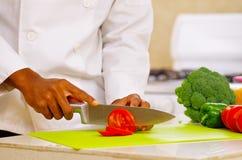 Zbliżenie ręki ciie kolorowych warzywa w fachowej kuchni szef kuchni, biały tło Zdjęcia Stock