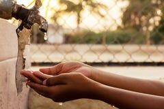 Zbliżenie ręki, dziecko woda pitna bezpośrednio od korporacji wody kranowej w India zdjęcia royalty free