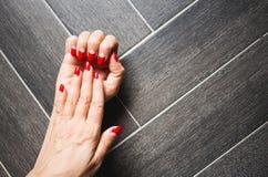 Zbliżenie ręki kobieta z zmrokiem - czerwony manicure na gwoździach przeciw ciemnemu drewnianemu tłu zdjęcia royalty free