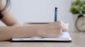 Zbliżenie ręki kobiety nauka i uczenie pisze w żywym pokoju w domu notatniku i dzienniczku zbiory
