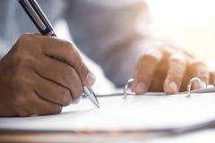 Zbliżenie ręki męski starszy writing Podpisuje kontrakt obrazy stock