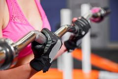 Zbliżenie ręki młoda kobieta robi ćwiczeniom z barbell w gym Zdjęcia Stock