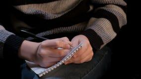 Zbliżenie ręki młody człowiek z notepad i czarnym ballpoint piórem Facet chce pisać coś ale no może myśleć, zbiory