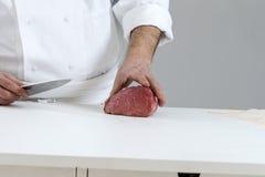 Zbliżenie ręki masarki rozcięcia plasterki surowy mięso z wielkiego loin dla tournedos Obraz Stock