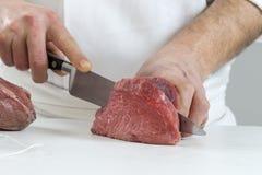 Zbliżenie ręki masarki rozcięcia plasterki surowy mięso z wielkiego loin dla tournedos Zdjęcie Stock