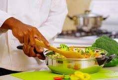 Zbliżenie ręki miesza wpólnie kolorowych warzywa w metal rynience szef kuchni, fachowa kuchnia, biały tło Obrazy Stock