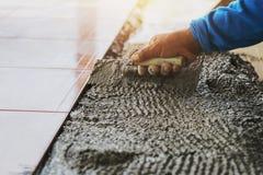 zbliżenie ręki pracownik budowlany kłaść płytkę zdjęcie royalty free