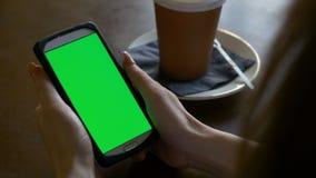 Zbliżenie ręki trzyma mądrze telefon z chroma klucza zieleni ekranem w kawiarni kobieta zbiory