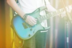 Zbliżenie rockstar na scenie bawić się na electro gitarze Męski gitarzysta w białej koszula obrazy royalty free