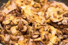 Zbliżenie rozciekły ser, pieczarki i cebule na hamburgerach, Fotografia Royalty Free