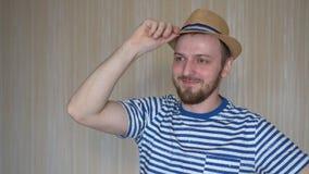 Zbliżenie rozochocony młody człowiek w kapeluszowej pozycji i ono uśmiecha się zbiory