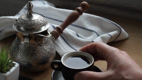 Zbliżenie samiec wręcza dolewanie kawę od czajnika w małą filiżankę, mężczyzna pije kawę zbiory