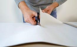 Zbliżenie samiec wręcza przygotowywać nową bended tapetową rolkę z nożycami na stołowy salowym zdjęcia stock
