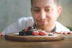 Zbliżenie skoncentrowany męski ciasto szef kuchni dekoruje deser wewnątrz zdjęcie stock