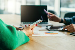 Zbliżenie smartphone w kobiety ` s rękach Młody bizneswomanu obsiadanie przy stołem i use smartphone zdjęcie stock
