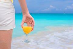 Zbliżenie sok pomarańczowy w żeńskiej ręce na tle morze Zdjęcia Stock