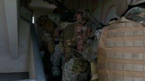 Zbliżenie specjalna wojsko sił jednostka wchodzić do w rujnującym budynku w poszukiwaniu wysokiego ceniącego terrorystycznego cel zdjęcie wideo