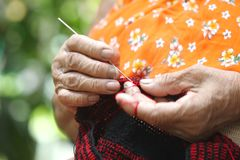 Zbliżenie stara kobieta w wsi, Tajlandia dzianie dziewiarską igłą i przędza robi handmade torbom przy ona do domu, czerwona i cza fotografia royalty free