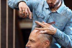 Zbliżenie starszy mężczyzna ma ostrzyżenie w zakładzie fryzjerskim Zdjęcie Stock
