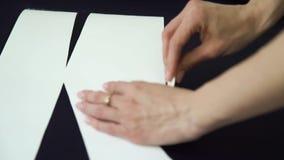 Zbliżenie stojaka ostrość kobieta krawczyna wręcza rysunkowego szablon na tkaninie zbiory