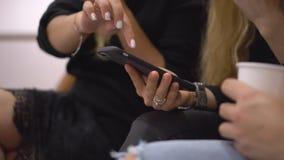 Zbliżenie strzał żeńskie ręki Kobiety siedzą przy konferencją z telefonami Kobiety piszą puszek informaci one w telefonie zbiory