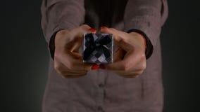 Zbliżenie strzał kobieta wręcza trzymać małego prezenta pudełko zawija z popielatym faborkiem zbiory