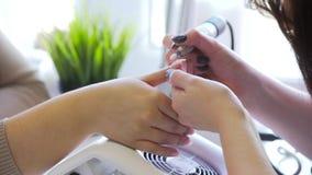 Zbliżenie strzał narzędzia manicure w piękno salonie Manicurzysta stosuje elektrycznego gwóźdź kartoteki świder manicure dalej zdjęcie wideo