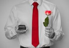 Zbliżenie strzał proponuje z pierścionkiem zaręczynowym w czarny i biały i różą mężczyzna Krawat i róża odizolowywający z kolorem obrazy royalty free