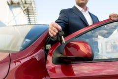Zbliżenie strzał przystojny samochodowy sprzedawca daje kluczom Zdjęcie Stock