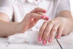 Zbliżenie strzał ręki stosuje moisturizer Piękno kobieta trzyma szklanego słój skóry śmietanka zdjęcie stock