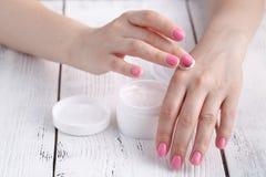 Zbliżenie strzał ręki stosuje moisturizer Piękno kobieta trzyma szklanego słój skóry śmietanka zdjęcie royalty free