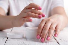 Zbliżenie strzał ręki stosuje moisturizer Piękno kobieta trzyma szklanego słój skóry śmietanka obrazy royalty free