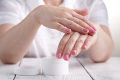 Zbliżenie strzał ręki stosuje moisturizer Piękno kobieta trzyma szklanego słój skóry śmietanka fotografia royalty free