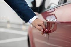 Zbliżenie strzelał młody biznesmen ciągnie samochodową drzwiową rękojeść Fotografia Royalty Free