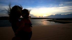 zbliżenie sylwetki matka Trzyma Małe dziewczyn fotografie Jeziorne przy zmierzchem zbiory
