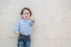 Zbliżenie szczęśliwy azjatykci dzieciak z eyeglasses przedstawienia cukierkiem w jego ręce na marmurowym kamiennej ściany texture zdjęcie royalty free